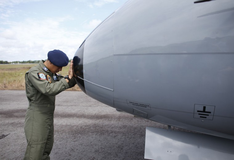 "A crew member of an Indonesian Maritime Surveillance plane says a prayer before a search mission to look for AirAsia's Flight QZ8501 in Pangkal Pinang, Bangka island December 30, 2014. Indonesian rescuers saw bodies and luggage off the coast of Borneo island on Tuesday and officials said they were ""95 percent sure"" debris spotted in the sea was from a missing AirAsia plane with 162 people on board. Indonesia AirAsia's Flight QZ8501, an Airbus A320-200, lost contact with air traffic control early on Sunday during bad weather on a flight from the Indonesian city of Surabaya to Singapore. (Darren Whiteside/Reuters)"