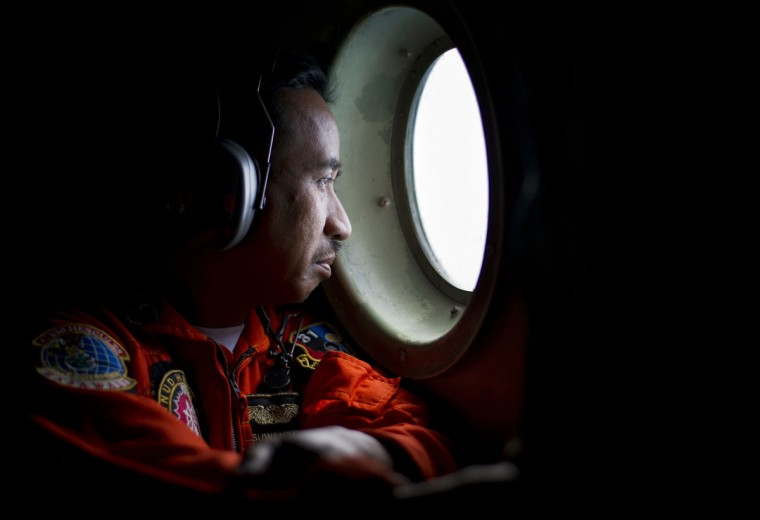 A member of an Indonesian Hercules C130 aircrew watches through a window while monitoring the Belitung Timur sea during search operations for AirAsia flight QZ8501 near Belitung island, December 29, 2014 in this photo taken by Antara Foto. (Wahyu Putro/Reuters)
