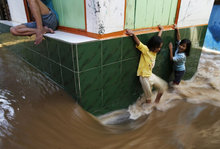 Children try to walk through a flooded street at Kampung Melayu residential area in Jakarta, December 23, 2014. Torrential rains that have continued in Indonesia in recent days have widened the number of flooded areas that include Jakarta and Bandung, a local newspaper said on Tuesday. (REUTERS/Beawiharta)