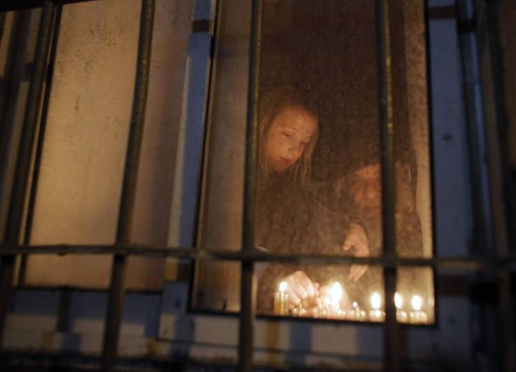 An Ultra-Orthodox Jewish boy lights a candle on the sixth night of the holiday of Hanukkah in Jerusalem's Mea Shearim neighborhood December 22, 2014. (Ammar Awad/Reuters)