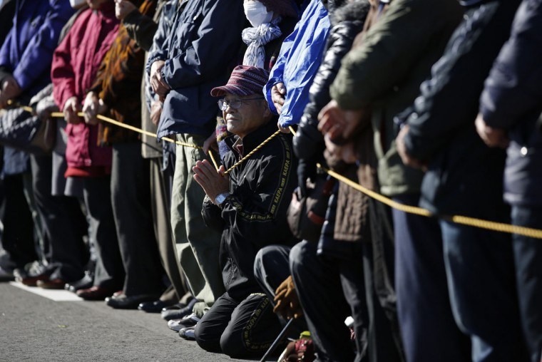 Voters wait for Japan's Prime Minister Shinzo Abe, who is also leader of the ruling Liberal Democratic Party (LDP), during his official campaign kick-off for the December 14 lower house election, at the Soma Haragama fishing port in Soma, Fukushima prefecture, December 2, 2014. (REUTERS/Issei Kato)
