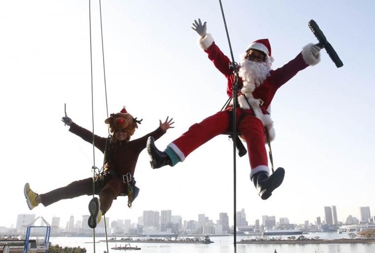 Window cleaners dressed as Santa Claus and a reindeer pose for pictures during an event to celebrate Christmas at a shopping mall in Tokyo. (Yuya Shino, Reuters photo)