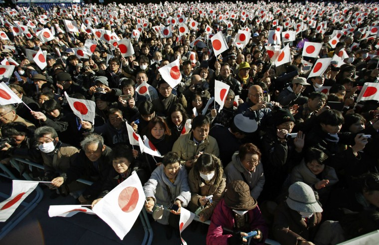 Well-wishers wave the Japanese national flags to celebrate Japan's Emperor Akihito's 81st birthday at the Imperial Palace in Tokyo December 23, 2014. (REUTERS/Issei Kato)