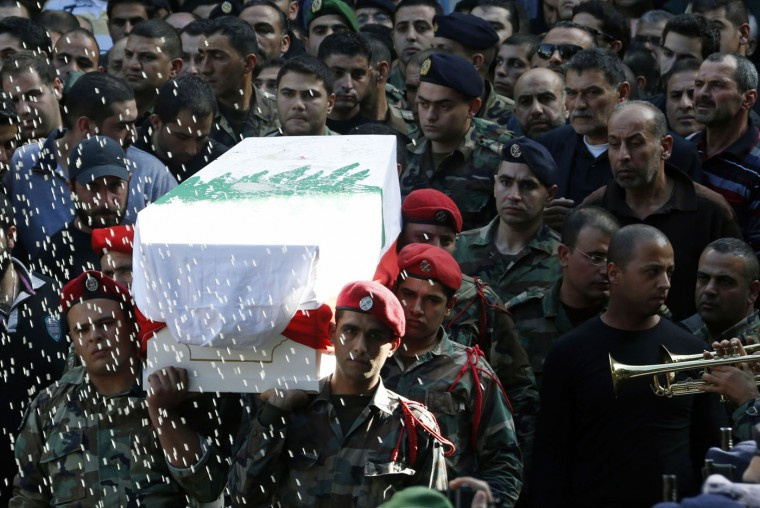 Rice is thrown as Lebanese army soldiers carry the coffin of Lebanese army adjutant Mahmoud Nurredin, who was killed while dismantling an explosive device outside the town of Arsal on the border with Syria on Wednesday, during his funeral in the town of Kafarman, southern Lebanon December 4, 2014. REUTERS/Ali Hashisho