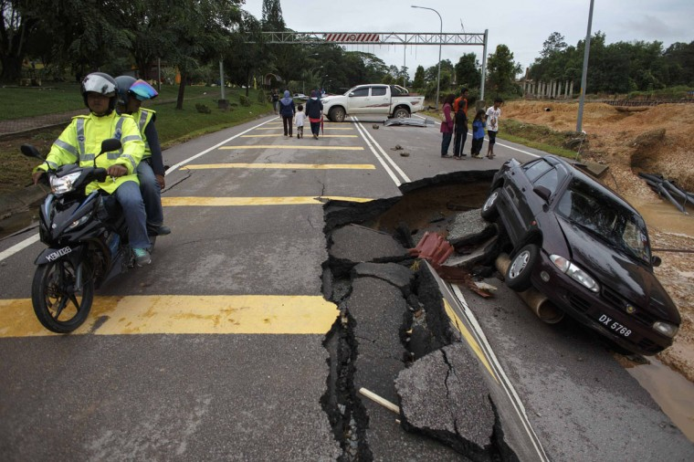 People ride past a road damaged by flooding at Kuala Krai in Kelantan December 30, 2014. The worst flooding in Malaysia in more than a decade has killed 10 people and forced nearly 160,000 from their homes and more rain is expected, authorities said on Sunday. (Athit Perawongmetha/Reuters)