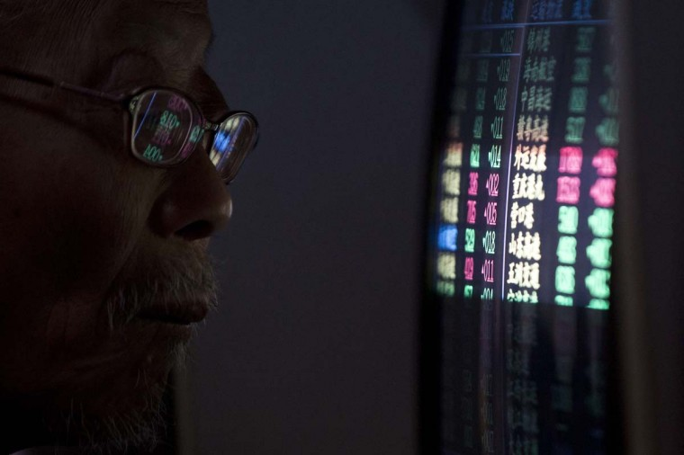 An investor looks at a computer screen showing stock information an a brokerage house in Shanghai, December 15, 2014. China stocks clawed back early losses and ended higher on Monday as a rally led by machinery manufacturers and transportation offset weakness in blue-chip financials. (Aly Song/Reuters)