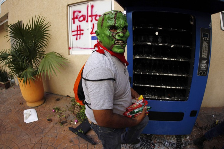 A masked CETEG (State Coordinator of Teachers of Guerrero) member loots a vending machine during a protest demanding the government find of missing students of the Ayotzinapa Teacher Training College Raul Isidro Burgos, at the General Attorney building in Chilpancingo, in the southern Mexican state of Guerrero December 1, 2014. Embattled President Enrique Pena Nieto on Thursday vowed to simplify Mexico's chaotic police structure and stop collusion between officials and drug gangs as he tried to defuse anger over the apparent massacre of 43 students in September. (REUTERS/Jorge Dan Lopez)