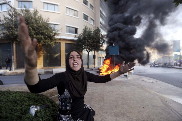 Wadha al-Sayyed, wife of captive Lebanese soldier Khaled Moqbel, protests for his release and government action, near burning tyres blocking a road in Beirut, December 15, 2014. More than two dozen members of the Lebanese security forces are being held by Sunni Islamists. (/Hasan Shaaban/Reuters)