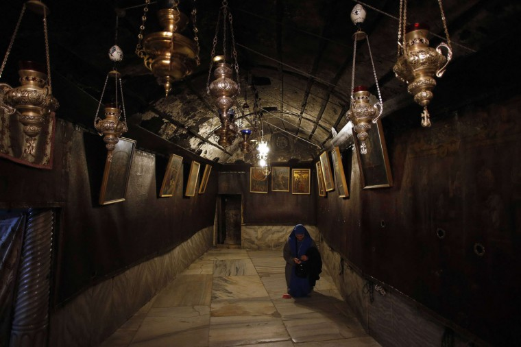 A Christian worshipper is seen inside the Grotto, where Christians believe Virgin Mary gave birth to Jesus, at the Church of Nativity ahead of Christmas in the West Bank town of Bethlehem December 17, 2014. REUTERS/Ammar Awad