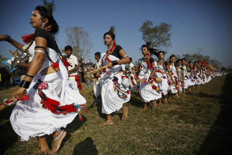 Tharu performers dressed in traditional attire participate in a parade marking an Elephant Festival event at Sauraha in Chitwan, about 170 km (106 miles) south of Kathmandu December 26, 2014. Elephants and mahouts from Chitwan will participate in the Elephant festival, which involves elephant races, elephants playing an exhibition soccer match and taking part in various other sporting activities. The event will start from 26th December and will end on 30th December 2014. REUTERS/Navesh Chitrakar