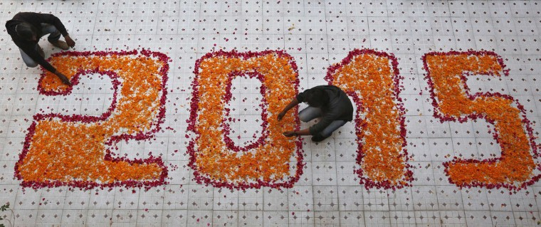 School teachers arrange flower petals in a formation during their New Year's Day celebrations at a school in the western Indian city of Ahmedabad December 31, 2014. REUTERS/Amit Dave