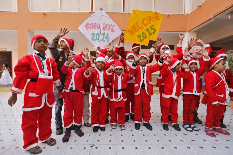 School students dressed in Santa Claus costumes pose during their New Year's Day celebrations at a school in the western Indian city of Ahmedabad December 31, 2014. REUTERS/Amit Dave