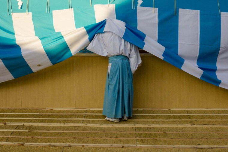 A Shinto priest looks behind a cover during ceremonies bidding farewell to 2014, ahead of New Year's Day, at the Meiji Shrine in Tokyo December 31, 2014. (Thomas Peter/Reuters photo)