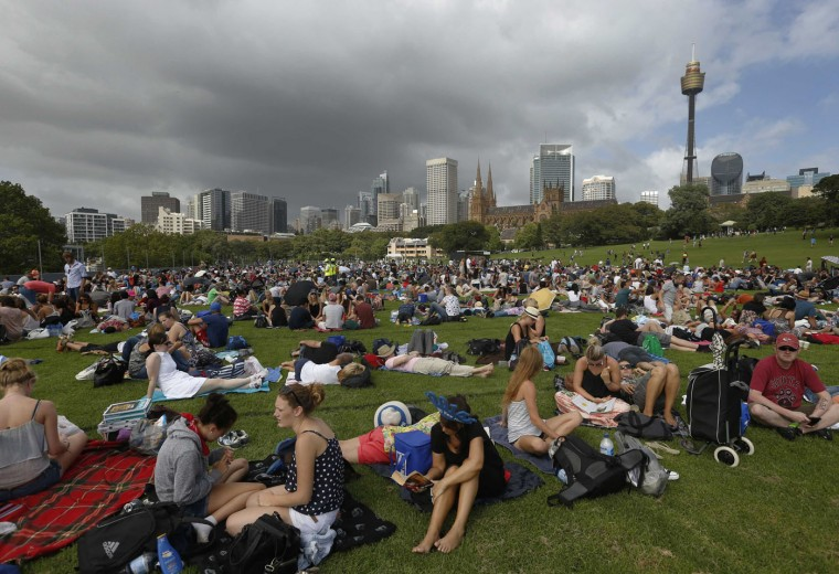 Thousands gather in a field near Sydney's Central Business District early December 31, 2014 as they wait for a harbourside vantage point to open to the public for New Year's Eve fireworks December 31, 2014. REUTERS/Jason Reed