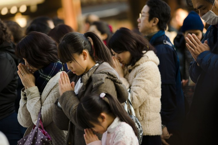 People pray during ceremonies bidding farewell to 2014, ahead of New Year's Day, at the Meiji Shrine in Tokyo December 31, 2014. REUTERS/Thomas Peter