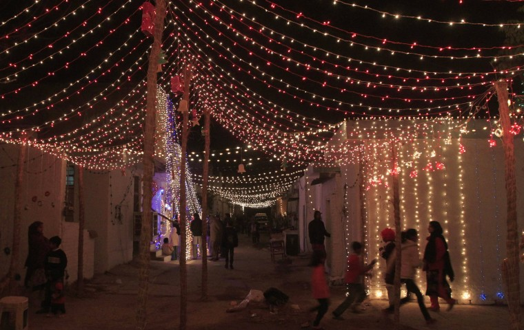 Children play in a street illuminated with lights on Christmas eve in a Christian slum in Islamabad December 24, 2014. REUTERS/Faisal Mahmood