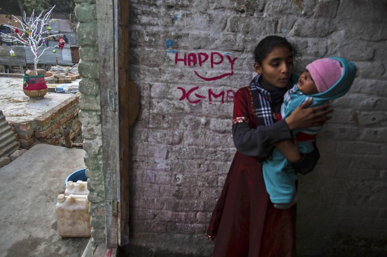A girl carries her nephew at her house in a Christian slum in Islamabad on Christmas eve December 24, 2014. REUTERS/Zohra Bensemra