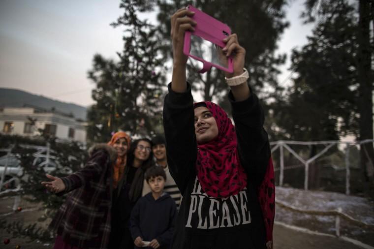 Muslims take a selfie near a Christmas tree ahead of Christmas in a Christian slum in Islamabad December 24, 2014. REUTERS/Zohra Bensemra