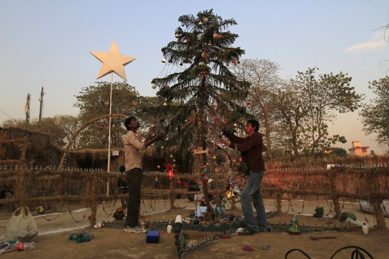 Girls talk to each other as they sit at their house beside a Christmas tree in a Christian slum in Islamabad on Christmas eve December 24, 2014. REUTERS/Zohra Bensemra