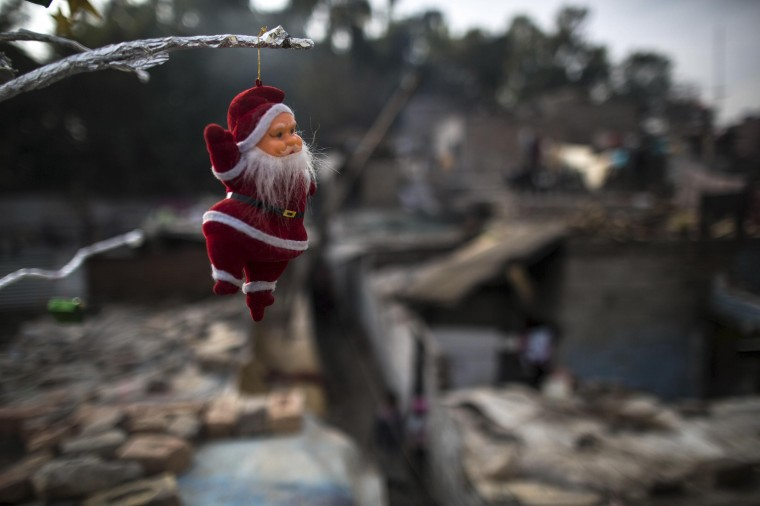 A Santa Claus figurine hangs from a tree ahead of Christmas in a Christian slum in Islamabad December 24, 2014. REUTERS/Zohra Bensemra