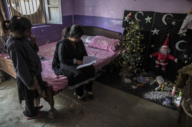 A teenager studies at her house ahead of Christmas in a Christian slum in Islamabad December 24, 2014. REUTERS/Zohra Bensemra