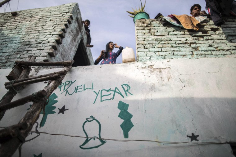 A Christian family is seen atop of their house ahead of Christmas in a Christian slum in Islamabad December 24, 2014. REUTERS/Zohra Bensemra