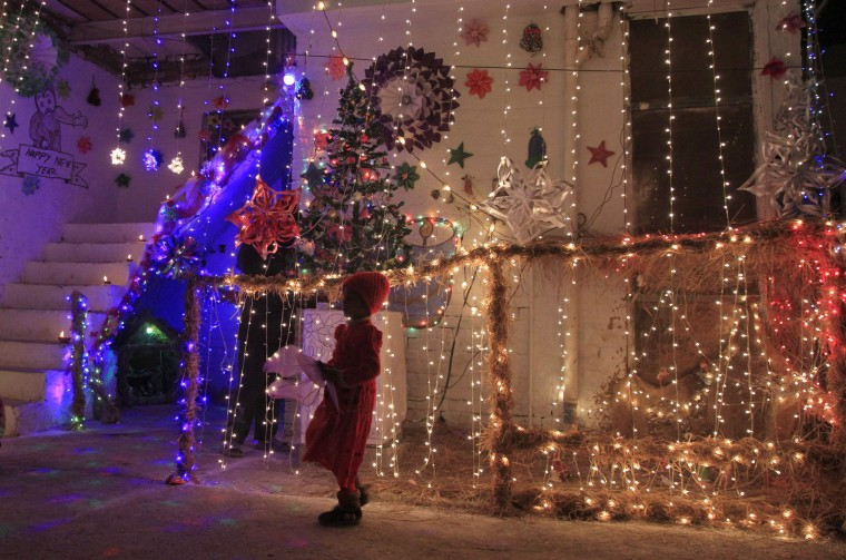 A girl stands outside a house illuminated with lights on Christmas eve in a Christian slum in Islamabad December 24, 2014. REUTERS/Faisal Mahmood
