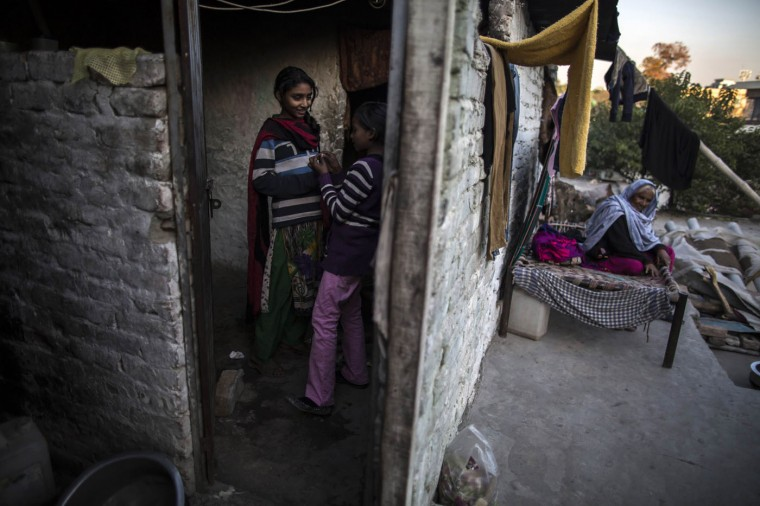 Girls talk to each other in their one-room shack while their grandmother sits outside, in a Christian slum in Islamabad December 4, 2014. REUTERS/Zohra Bensemra