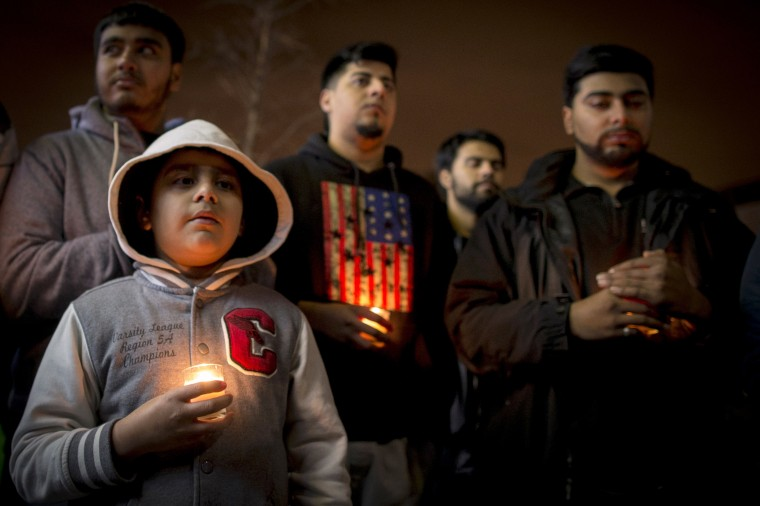 People hold candles during a vigil for victims killed in the attack by Taliban gunmen on the Army Public School in Peshawar Pakistan, in the Brooklyn borough of New York December 17, 2014. Pakistan on Wednesday began burying 132 students killed in a grisly attack on their school by Taliban militants that has heaped pressure on the government to do more to tackle an increasingly aggressive Taliban insurgency. REUTERS/Brendan McDermid