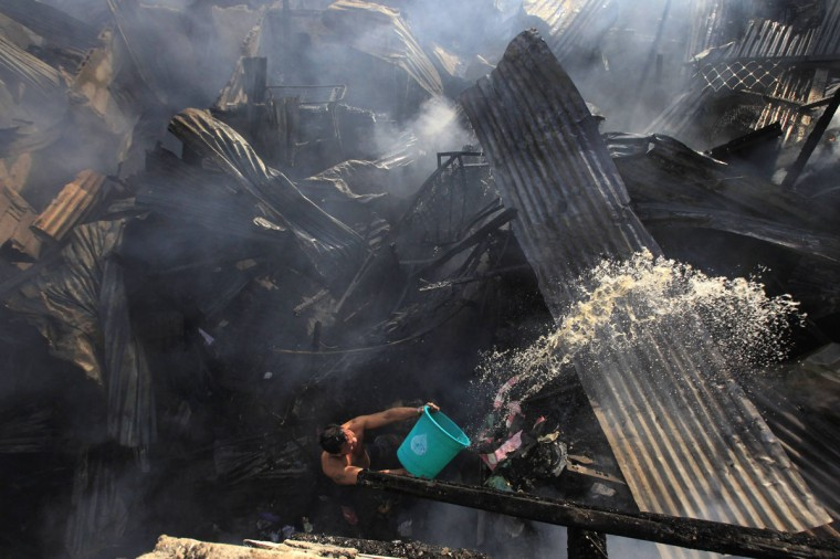A man uses a pail of water to help out firefighters as they try to put out a fire that broke out at a slum area in Manila December 11, 2014. Around 200 houses were gutted by the fire in the early morning of Thursday, which left an estimated 500 families homeless and one firefighter injured, local media reported. (Romeo Ranoco/Reuters)