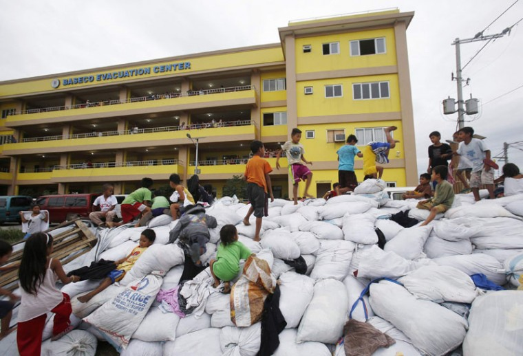 Children play atop sacks of donated clothes at an evacuation centre for the coastal community to take shelter from Typhoon Hagupit, in Manila December 8, 2014. Hundreds of thousands of Filipinos began to return to their homes battered by a powerful typhoon at the weekend, but the nation collectively breathed a sigh of relief as a massive evacuation plan appeared to minimize fatalities. The death toll from typhoon Hagupit stood at four on Monday, as over a million people escaped the wrath of the Category 3 storm in evacuation centers across the center of the country, although hundreds of homes were flattened. (Cheryl Gagalac/Reuters)