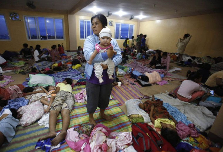 A mother carries her baby while others rest at an evacuation centre for the coastal community, to shelter from typhoon Hagupit, in Manila December 8, 2014. Typhoon Hagupit weakened to a tropical storm as it churned close to the Philippine capital on Monday, after killing 27 people on the eastern island of Samar island where it flattened homes, toppled trees and cut power and communications. (Cheryl Gagalac/Reuters)