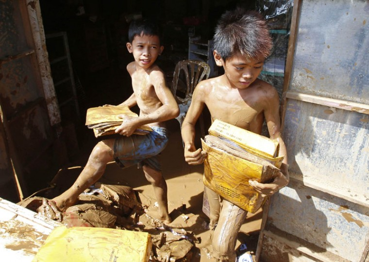 Boys recover school materials in a house inundated by mud brought by Typhoon Hagupit in Borongan city, Samar, in central Philippines December 8, 2014. At least 21 people were reported dead, many of them drowned as flood waters rose in Borongan, the main town in Eastern Samar, where typhoon Hagupit made first landfall, the Philippine National Red Cross said on Monday. The Philippines had evacuated more than a million people as the powerful typhoon approached the country from the Pacific, fearing a repeat of a super storm last year that left more than 7,000 dead or missing. (Erik De Castro/Reuters)