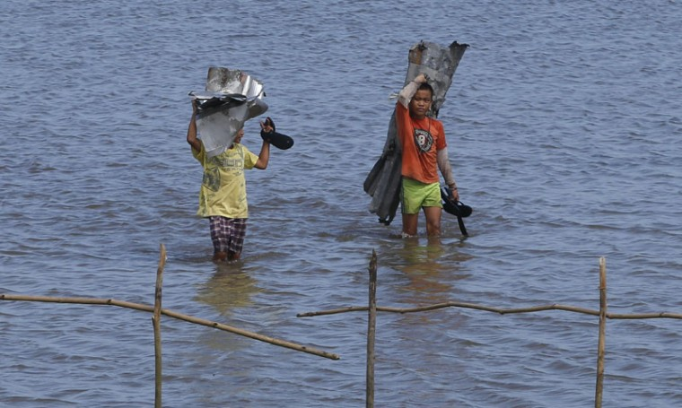 Residents carry roofing metal sheets swept at the height of Typhoon Hagupit in Dolores, Samar, in central Philippines December 8, 2014. At least 21 people were reported dead, many of them drowned as flood waters rose in Borongan, the main town in Eastern Samar, where typhoon Hagupit made first landfall, the Philippine National Red Cross said on Monday. The Philippines had evacuated more than a million people as the powerful typhoon approached the country from the Pacific, fearing a repeat of a super storm last year that left more than 7,000 dead or missing. (Erik De Castro/Reuters)