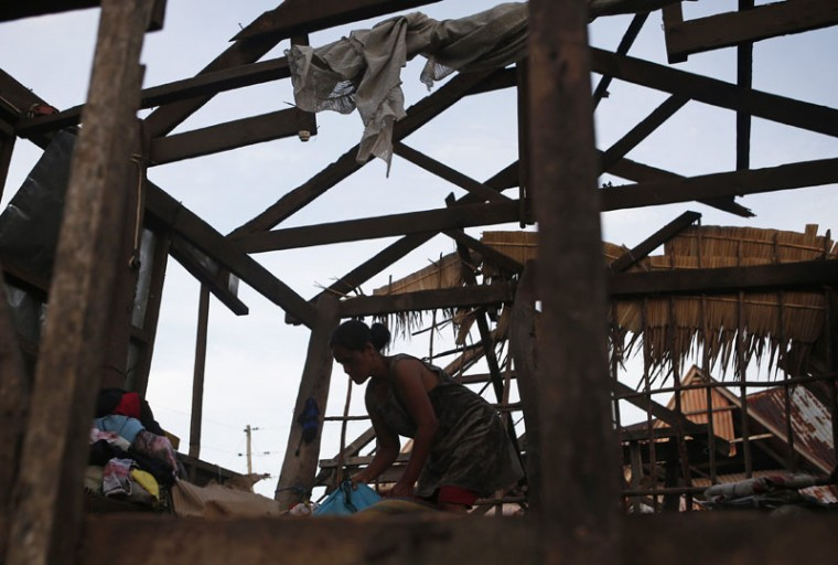 A typhoon victim recover clothes in the remains of her house in Dolores, Samar, in central Philippines December 8, 2014. At least 21 people were reported dead, many of them drowned as flood waters rose in Borongan, the main town in Eastern Samar, where typhoon Hagupit made first landfall, the Philippine National Red Cross said on Monday. The Philippines had evacuated more than a million people as the powerful typhoon approached the country from the Pacific, fearing a repeat of a super storm last year that left more than 7,000 dead or missing. (Erik De Castro/Reuters)