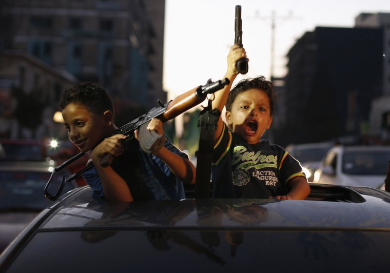 Palestinian children hold guns as they celebrate with others what they said was a victory over Israel, following a ceasefire in Gaza City in this August 26, 2014 file photo. I was covering the celebrations by Palestinians moments after the declaration of a ceasefire that ended a 51-day fighting between Israel and Hamas. Throwing sweets and chanting slogans, people took to the streets, riding vehicles and motorcycles, to celebrate what they said was victory over Israel. Moments before taking this picture, the battles between Israel and Gaza's militants were taking place and explosions could be heard till the truce was announced. The scene was special as children were smiling, holding a pistol and weapon, and showing no sign of fear. It was quite difficult to take the picture since there was not enough light, and the car was driving quickly. My movement was also restricted due to the traffic jams and flows of people in the streets. - Suhaib Salem