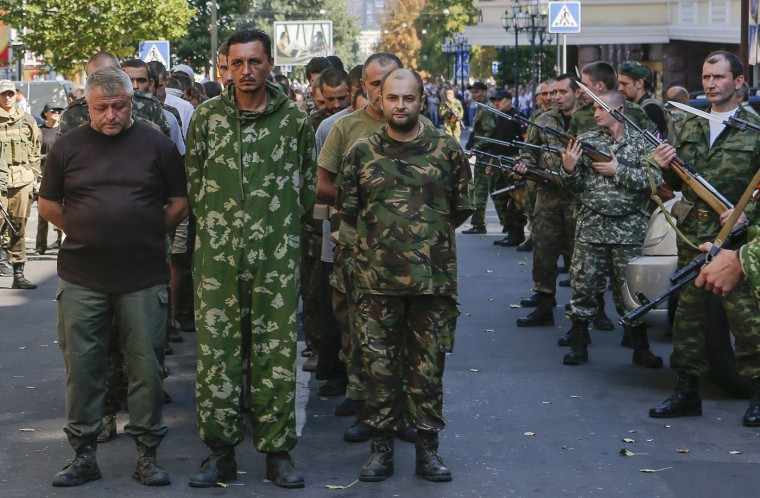 Armed pro-Russian separatists (R) escort a column of Ukrainian prisoners of war as they walk across central Donetsk in this August 24, 2014 file photo. It was an awful sight: A column of jaded and haphazardly dressed people walking along the street surrounded by armed rebels. Citizens were shouting curses and throwing eggs at them. The column was followed by street sweepers washing the road after the prisoners. The scene looked like a farce or copy of the parade of German prisoners in World War Two in Moscow in 1945. I think this image perfectly shows the negative emotions of conflict: weakness, devastation, shame, fear on one side and spite, aggression, rage and desire for revenge on the other. It reminded of a quote 'History repeats itself, first as a tragedy, second as a farce'. - Maxim Shemetov