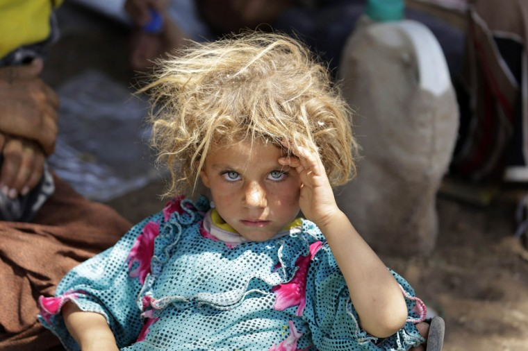 A girl from the minority Yazidi sect rests after fleeing violence in Sinjar, in this August 13, 2014 file photo. I remember the scene well. It was the day that I arrived at the Iraqi-Syrian border crossing of Fishkhabour. With shocked, sunburnt faces, men, women and children in dirt-caked clothes were struggling in temperatures of over 45 degrees Celsius (113 Fahrenheit). At first, I focused my camera on a group of women sitting on the ground, but when I turned away I saw this little girl. I took one shot of her there and as she saw me, she gave me a smile. I captured another frame of her with her mother. I was drawn to her wild beauty in this terrible situation. There is a kind of intensity, distress and sadness in her eyes. It was really sad not only to see this girl, but also to see the hundred others who were dirty, exhausted, and sitting amongst garbage in the heat. I would be very curious to see the blonde girl who I photographed again. I wonder what will become of her. I wonder what will become of all the others. - Youssef Boudlal