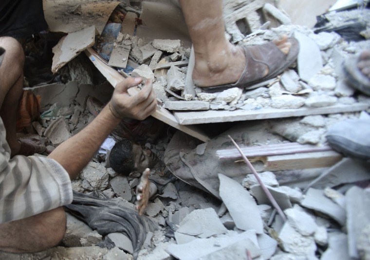 """Palestinians rescue Mahmoud al-Ghol from under the rubble of a house in Rafah in the southern Gaza Strip in this August 3, 2014 file photo. I was at a house with my colleagues monitoring the situation in Rafah, when I heard two huge explosions. The shout went up: """"A hit by Israeli F16!"""" Once I realised that the house had an asbestos roof, I knew there would be serious casualties. First they removed the body of an old man and then people started to shout: """"Children under the rubble!"""" I rushed to the closest position to photograph these kids. The boy in this picture was later identified as Mahmoud al-Ghol. He is 10 years old. Nine of Mahmoud's relatives, including his uncle's family, were killed in the strike and another seven were wounded. Seeing him beneath the debris was the worst experience of my life. Tears were running from my eyes while I was taking the pictures. Looking at the boy was like looking at my own son. A colleague of mine knows Mahmoud's relatives and after the strike he helped me to trace him to where he was being treated in hospital. - Ibraheem Abu Mustafa"""