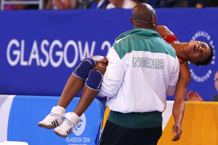 Ifeoma Nwoye of Nigeria is carried away by her coach after she lost her women's freestyle 55kg wrestling semi-final at the 2014 Commonwealth Games in Glasgow, Scotland, in this July 31, 2014 file picture. The picture was shot during the Commonwealth Games in Glasgow. In the image, the wrestler's coach is carrying her away after she lost her bout. It was not immediately clear to me whether she had been injured in the contest or whether she was simply upset at having lost. The Nigerian woman lost and was knocked out of the competition by the eventual gold medallist who easily overpowered her. There was a moment of serendipity as I followed the coach and wrestler out as the games logo formed a halo around her head which helps the viewer focus on the expression on her face. The whole moment was over in a second, and the tournament carried on. If anything I suppose the picture shows that sometimes in sport a moment of crushing disappointment can be just as engaging as a moment of victory. - Andrew Winning