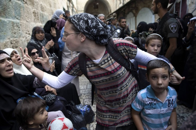 An Israeli woman (C) and a Palestinian woman gesture at one another during a protest by Palestinian women against Jewish visitors to the compound known to Muslims as Noble Sanctuary and to Jews as Temple Mount in Jerusalem's Old City in this October 14, 2014 file photo. The Palestinian women were singing and chanting in Arabic while heavily armed Israeli border police looked on and occasionally pushed them back to make way for Jewish worshipers going to the Western Wall. The Palestinian women shouted and harassed Jewish passersby while Orthodox Jews living in apartments above the street threw bottles and water down at the Palestinian women. About half a dozen Orthodox Jewish worshipers wanted to pass along the narrow street toward the Western Wall and the Israeli border police created a passageway through the crowd of Palestinian women. As the Israelis walked between the shouting protesters I focused on the woman in the center of the scene. When she was right in front of me, she turned and gestured to the Palestinian woman. It wasn't something done for the camera -- I don't think she even realized I was there. It was only when I looked at the picture afterward that I realized that the Palestinian woman had returned the gesture, which in this part of the world is the equivalent to giving someone the middle finger. - Finbarr O'Reilly