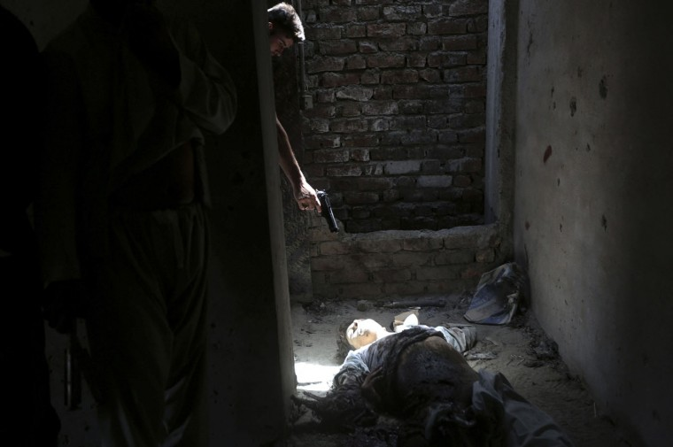 An Afghan resident points his weapon at the dead body of an unidentified militant, as a way of showing his hatred for insurgents, after an attack on Kabul airport in this July 17, 2014 file photo. Militants armed with rocket-propelled grenades attacked Kabul International Airport from the roof of a building just to its north. Such attacks are not uncommon in Kabul and I have photographed quite a number of these incidents. After four or five hours of fighting between Taliban and Afghan security forces, all insurgents were killed and curious locals and media were allowed to enter the site. A group of unidentified men armed with guns were looking around the bodies of the dead Taliban, some of them were kicking the bodies, some cursing. One of them pointed his gun at the body of the Taliban fighter who was lying at the scene. I shot the frames quickly and moved back thinking he might fire and the impact could get to me. He did not fire. - Omar Sobhani