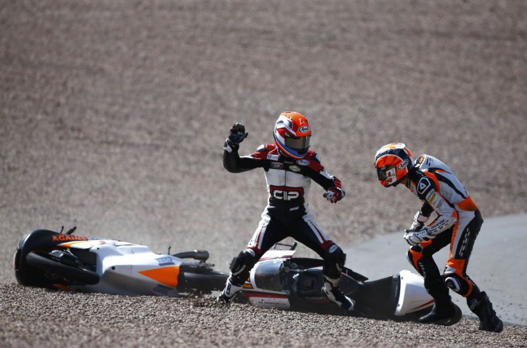 Mahindra Moto3 rider Bryan Schouten of the Netherlands fights with compatriot Kalex KTM Moto3 rider Scott Deroue (R) after they crashed during the German Grand Prix at the Sachsenring circuit in Hohenstein-Ernstthal in this July 13, 2014 file photo. During lap 26, towards the end of the race, I was standing behind the tire barrier in the first bend waiting for the pack of riders. I decided to make this lap the last one before changing position to shoot the winner crossing the finishing line further up the track. When the pack approached, two riders came skidding out of the pack, losing contact with their bikes and coming to a halt in the gravel traps a mere two metres away from each other. It was impossible to make what had actually happened as the incident that led to the crash was obscured by the other riders. But Schouten seemed to be sure who was to blame. He jumped to his feet and started to lay into his compatriot, Scott Deroue, kicking and punching his helmet. After initially blocking the attack somewhat coyly, Deroue became equally furious and responded in kind. The two had to be separated by several medics and race attendants who struggled to bring the brawl to an end. - Thomas Peter