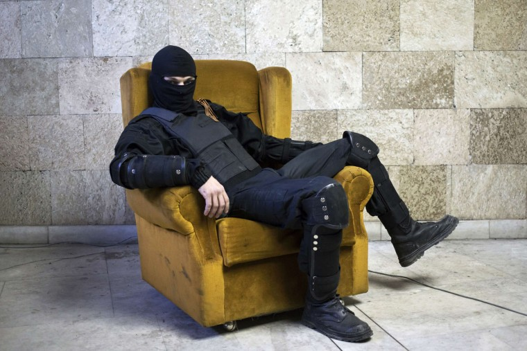 """A masked pro-Russian protester sits on a chair as he poses for a picture inside a regional government building in Donetsk, eastern Ukraine in this April 25, 2014 file photo. On March 3, a couple hundred pro-Russian demonstrators stormed the Donetsk regional government building after clashing with police who were guarding the main entrance. They successfully entered through a side door, and in the end made it to the second floor where the parliament sits. Unrest continued to spiral in Ukraine and the following month separatists declared a """"People's Republic of Donetsk"""". Two months after these initial attacks, protestors were still inside the regional government buildings and masked men guarded the barricades. I asked to take a series of portraits of these men. I saw a massive chair underneath a neon light and I picked my lens, adjusted the light, and people began to pose in shifts. Each subject was relaxed, and struck whatever pose suited him. Later, they asked with interest how people in Europe see the situation in Ukraine and wanted to know if anyone supports them, and what will happen in the end. They seemed a bit scared. I didn't have a good answer to their last question. - Marko Djurica"""