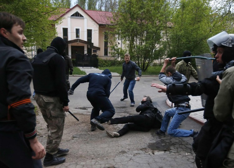 Pro-Russian protesters attack a pro-Ukranian protester during a pro-Ukrainian rally in the eastern city of Donetsk in this April 28, 2014 file photo. Around 500 people were waving Ukrainian flags and shouting anti-Russian slogans. After 30 minutes they started a protest march, but soon afterwards pro-Russian protesters turned up with baseball bats and sticks and clashes broke out. I followed pro-Ukrainians who ran away to small alley, but as there was no way out they got trapped. After some 30 seconds, pro-Russians came and started beating them. For me the image was important because it shows how easily people who were living together for years can turn violent overnight because of politics. Moments before I took this picture I remember I was hiding behind a tree because stones from both sides were flying around. I remember one stone hit Baz Ratner, our photographer who was covering the event with me. The biggest challenge while shooting this image was to not get beaten, because people were extremely violent and they didn't care if you were a journalist. - Marko Djurica