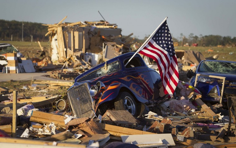 A U.S. flag sticks out the window of a damaged hot rod car in a suburban area after a tornado near Vilonia, Arkansas in this April 28, 2014 file photo. I was covering the tornados that swept though Arkansas and other states killing 35 people and I decided to drive out to Vilona, an area that had suffered some of the worst damage, having seen it from a plane. Gaining access into the area was difficult and I arrived quite late in the day so most of the rescue efforts had ceased, but I felt it was an important story to tell. I was walking around when I noticed the vintage hot-rod on a pile of rubble that had been a house, and I thought it was a good image to demonstrate American resilience and courage in the face of such a disaster. I had to crawl over the debris so I could get a photo of the front of the car with the flag out the window and some of the other houses in the background that had been destroyed. I was affected by the image's story when I found out that the owner of the car and house, Dan Wasson, died in the tornado as he huddled over his wife and daughters in their home. - Carlo Allegri