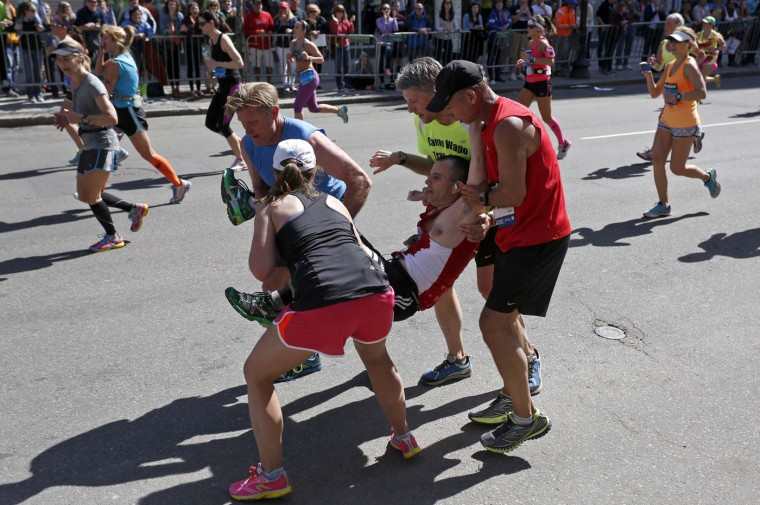 Four runners carry Adam Hurst down Boylston Street after his legs locked up during the 118th running of the Boston Marathon in Boston, Massachusetts in this April 21, 2014 file photo. I was positioned near the Forum restaurant in case anything significant happened at the time and place of last yearís second bomb attack. I heard the crowd starting to make noise and noticed a man struggling but still standing, legs locked after just having passed 26 miles. The cheers from the sidelines were louder than anything I had heard all day, urging him on, but his body wouldnít cooperate. Thatís when a man, I think David Meyer, stopped his run and offered help. Four runners decided to each take one of Hurst's limbs and haul him closer to the line. The moment Hurst's feet came off the ground the spectators erupted in a cheer and they set off faster than I was able to keep up with them on the sidewalk. Both as a journalist and a runner it mattered to me whether he finished on his own legs or theirs, but most importantly I knew it mattered to Hurst. The last thing I wanted was for him to see my picture published saying he didn't carry himself over that line. Some folks have pointed out that this sort of moment is almost commonplace in marathons, and that's partly true. But just because what happened that day on Boylston Street isn't unprecedented doesn't mean it isn't special. The moment I was fortunate to witness sums up so much of what I love about this city, this sport, and this event in particular. - Dominick Reuter