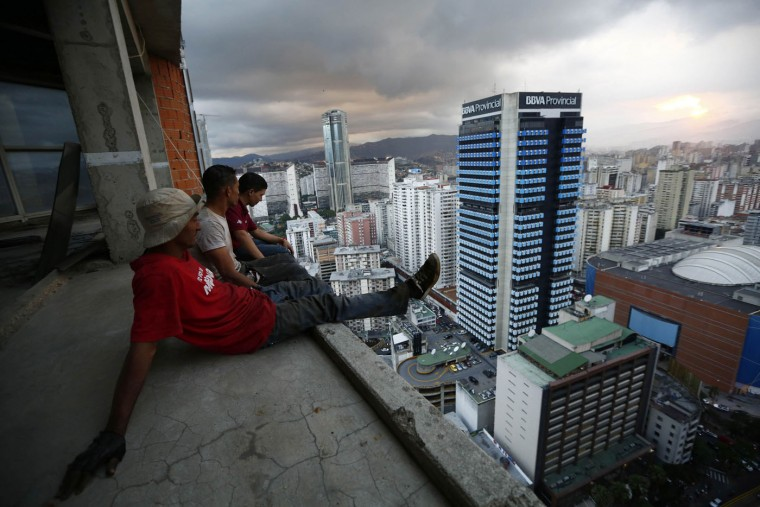 """Men rest after salvaging metal on the 30th floor of the """"Tower of David"""" skyscraper in Caracas in this February 3, 2014 file photo. The building was intended to be a shining new financial center but was abandoned around 1994 after the death of its developer and the collapse of the financial sector. Squatters invaded the huge concrete skeleton in 2007 and now about 3,000 people call the tower their home. The first time I tried to get access to the tower wasn't really a success. I was told, not in the friendliest of terms, that I should leave while I still could. The residents of the tower, and particularly those in charge of managing it, were (and still are) very sensitive to media. Publications frequently feature headlines such as: 'Tower of terror,' 'The shanty skyscraper,' it has even been featured in an episode of the TV series 'Homeland' as a kidnappers' den. My intention wasn't to follow on from these headlines. I wanted above all to create a portrait of the lives of the thousands of people who call this place home, and who face struggles and risks every day. I wanted to document without judging. That is what I told the squatters' board of administrators, who made me explain my intentions in producing this story. I felt the strong sense of community here from the first time I ascended the tower. - Jorge Silva"""