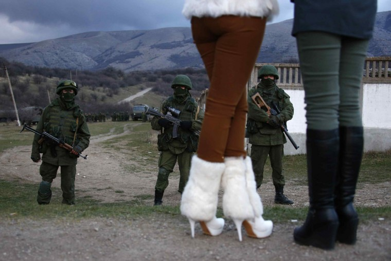 Local women watch armed men, believed to be Russian soldiers, assemble near a Ukrainian military base in Perevalnoe in this March 5, 2014 file photo. During Russia's occupation of the Crimean peninsular in Ukraine, masked men without insignia had appeared at Ukrainian army bases and important transport hubs all over the peninsular. Although they declined to say who they were, their Russian accents, military kit and license plates left little doubt that Moscow had sent them. The locals believed they would protect them from attackers from Kiev and consequently welcomed the Russian soldiers like liberators, bringing them flowers and food and flocking to wherever they set up base as if a travelling circus had come to town. These two women had clearly dressed up for the occasion and flirted with the young men in uniform, who were visibly grateful for the distraction to their sentry duty. Eventually, Russian soldiers became less anxious to be seen by foreign media chatting with their Ukrainian counterparts across the compound walls. - Thomas Peter