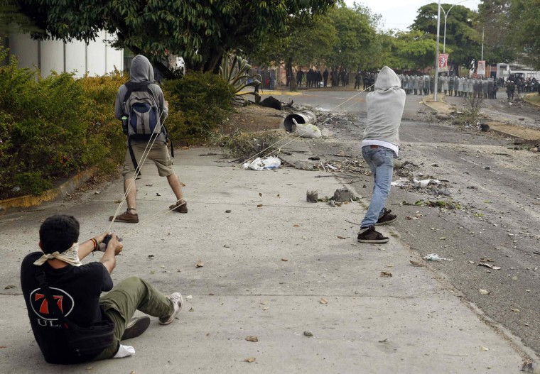 Demonstrators use a slingshot against the National Guard during a protest in San Cristobal, in this February 27, 2014 file photo. Following a couple of days of riots in Caracas, we decided to travel to the Venezuelan city of San Cristobal to photograph the conflict there. In the afternoon, I was told of clashes between anti-government protests and the National Guard, but barricades blocking almost every street made it extremely difficult to commute from one place to another, even by motorbike. When I finally arrived, it looked like the worst had passed as there was debris everywhere, but a group of youths with giant slingshots remained. With the help of their neighbours, who hurled objects from the top floors of buildings, they had driven the National Guard back to the end of the street. - Carlos Garcia Rawlins